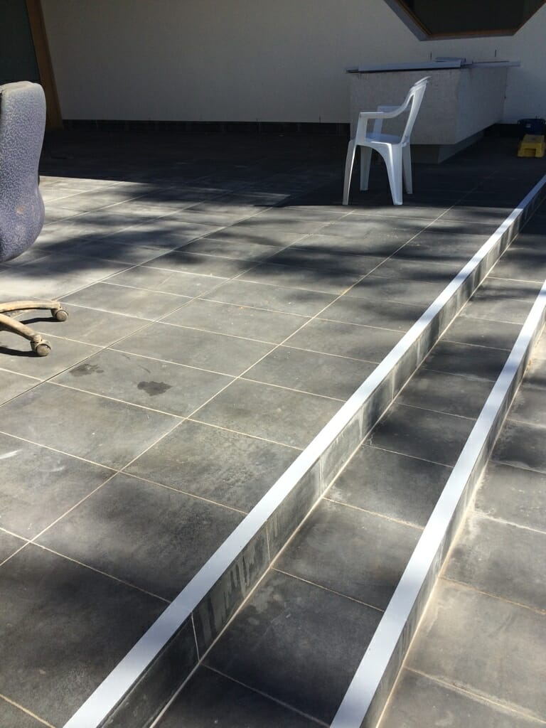 Grey tiled steps with white Ant-Slip safety tape